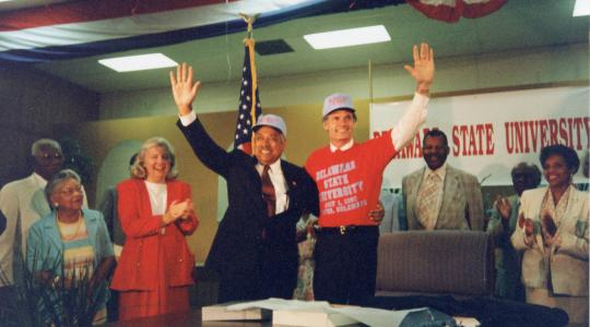 <p>On July 1, 1993, William B. DeLauder, president of Delaware State University, waves with Gov. Tom Carper at the signing of Senate Bill 138 which changed Delaware State College to Delaware State University. Looking on in the background, from left, are Senator Herman Holloway Sr., Hattie Mishoe, Representative Nancy Wagner, James C. Hardcastle and Vermell DeLauder.</p>