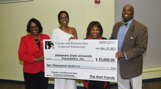 <p>Holding a display check for the newly established Chester and Ramona Hart Endowed Scholarship are (l-r) Dr. Vita Pickrum, Vice President of Institutional Advancement, Dana Hart-Raynor, University President Wilma Mishoe and Eric Hart.</p>