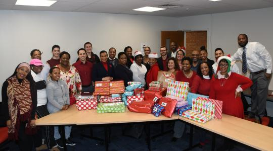 <p>The Office of Student Success staff shows the fruits of their benevolence -- Christmas gifts for two disadvantaged families it has adopted for this holiday season.</p>