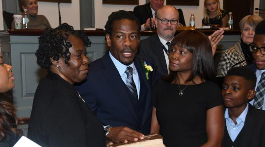 <p>Newly elected Rep. Nnamdi Chukwuocha, surrounded by his family, is sworn in as a member of the Delaware House of Representatives by Delaware Supreme Court Justice James T. Vaughn, Jr. The new legislator's mother Mary Jones (l) holds the bible while his wife Chica stands to his right.</p>