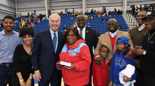 <p>Dr. Wilma Mishoe stands next to Wilmington Mayor Michael Purzycki as she is honored  by the city as part of their annual Black History Month celebration at the 76er Fieldhouse as part of the Long Island Nets vs. Delaware Blue Coats basketball game. Standing around them are city officials and DSU community members.</p>