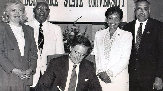 <p>Dr. Willliam B. DeLauder (far right), the University's eighth president, stands with state Rep. Nancy Wagner, state Sen. Herman Holloway Sr., and his wife Vermell, as then-Gov Tom Carper signed legislation renaming the College to Delaware State University. Dr. DeLauder passed away on May 21.</p>