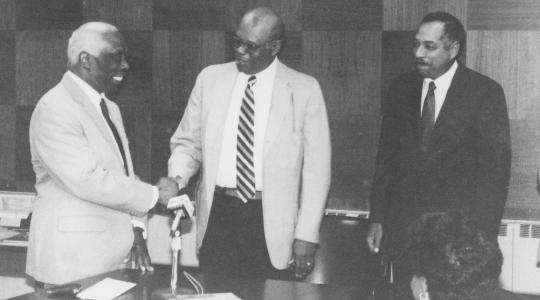 <p>The historic 1987 passing of the presidential torch between then-outgoing DSC President Luna I. Mishoe (l) and his successor Dr. William B. DeLauder (r). Then-Board of Trustees President William Dix (center) shakes Dr. Mishoe&#039;s hand.</p>