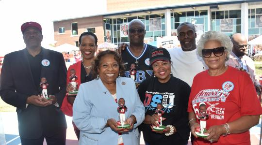 <p>Hornet football alumni and former NFL star John Taylor (2nd from the right) presents members of the University Board of Trustees and Dr. Wilma Mishoe with a signed bobble head likeness of himself.</p>