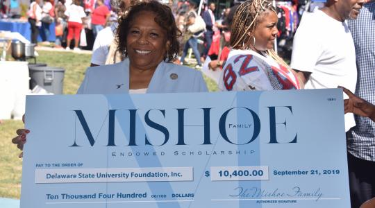 <p>University President Wilma Mishoe holds a display check on behalf of her family that signals the establishment of the Mishoe Endowed Scholarship.</p>