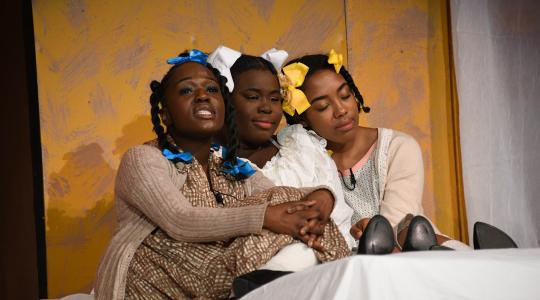 <p>(L-r) Claudia, Frieda and Pecola (performed by Zaire Davis, Chloe Humphrey and Elia Agudo, respectively) huddle together during a scene of the Bluest Eye, which took the stage at Delaware State University Oct. 31 and Nov. 1.</p>