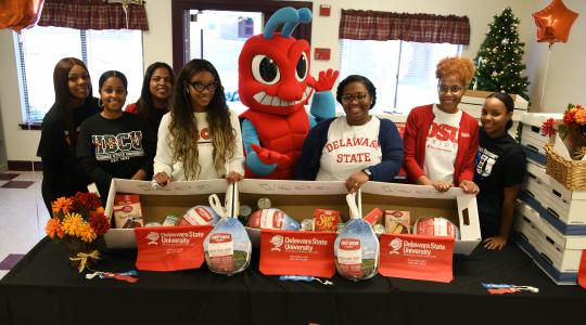 <p>These Enrollment Management members -- (l-r) Destiney Woodson, Shelvia Wright, Andrea Wilson, Siara Bey, the Too Fly Hornet Mascot, Melayna Hall, Tiara Dennis, and Gernelle Forrest -- distributed Thanksgiving dinner items in Smyrna. Another group of their colleagues did the same at a Dover location</p>
