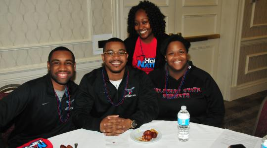 <p>Diane Kirby (standing), manager of DSU Alumni Engagement, poses with three young alums at the March 9 DSU Alumni Reception at the MEAC Tournament in Norfolk, Va.</p>