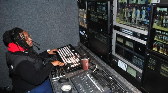 <p>Jasmine Alford works a Hornet basketball game in the Mobile Video Production Trailer. The production trailer has reduced the set-up time for the students and provided them with an excellent hand-on experience environment.</p>