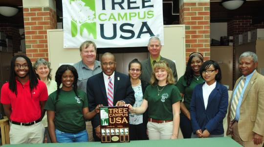 <p>Displaying DSU's Tree Campus USA designation, DSU President Harry L. Williams (center) is joined by DSU faculty members; Dr. Michael Valenti, state forestry administrator, and DSU students.</p>