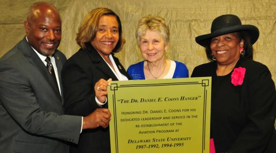 <p>(L-r) Lt. Col. Michael Hales, director of the DSU Aviation Program; College of Business Dean Donna Covington; JoAnn Coons, widow of Dr. Coons; Dr. Wilma Mishoe, DSU Board of Trustees member, hold a copy of the plaque that is being created for the Daniel E. Coons Hangar.</p>