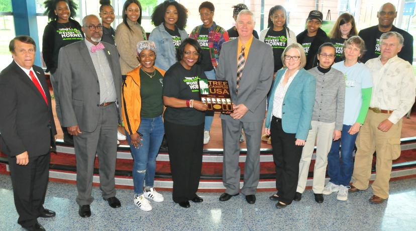<p>Dr. Vita Pickrum (center) receives the Tree Campus USA renewal designation on behalf of DSU from Dr. Michael Valenti, Delaware state forester. They are flanked by other DSU officials and Roteract and Interact student organizations.</p>