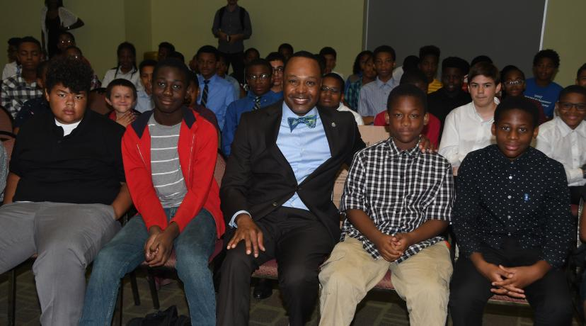 <p>James Collins (center), chief information officer for the State of Delaware and the keynote for the Verizon DSU Innovative Learning Presentation Day Program, poses with the middle school youths that participated in the three-week summer camp.</p>