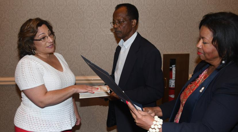 <p>New Board of Trustees member Margie Lopez Waite (l) is sworn in by Board Chair Dr. Devona Williams during the Sept. 20 meeting. Trustee Harold Stafford holds the bible.</p>
