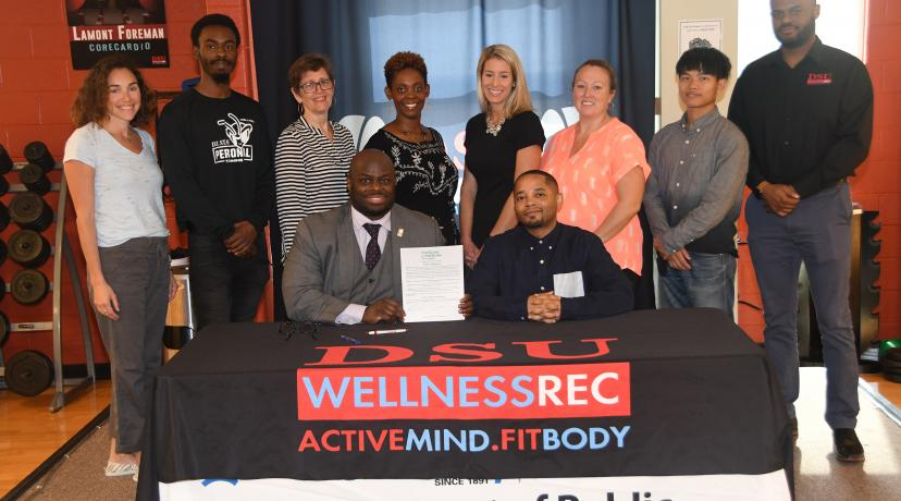 <p>University Provost Tony Allen, with Public and Allied Health Chair Dr. Chris Mason beside him and flanked by department members, WRC staff and other health enthusiasts, hold up the proclamation he just signed declaring that October is Exercise is Medicine Month on campus.</p>
