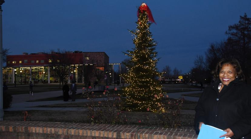 <p>University President Wilma Mishoe stands in from the campus Christmas tree, which she had just lit in a Dec. 3 ceremony outside of the Recreation and Wellness Center.</p>