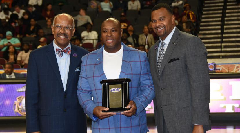 <p>Delaware State University's 2019 Distinguished Alumnus of the Year Ronnie Shaw Sr. (center), receives the award from Dr. Irving H. Smith (l), president of the MEAC Delegate Assembly, and James Church of Priority Automotive, tournament sponsor.</p>
