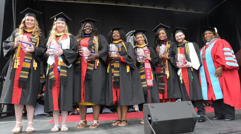 <p>Seven 4.0 GPA graduates -- (l-r) Micaela Cummings, Stephanie Lynn, Adriante Carter, Jazmyn Robinson Stockton, Jasmine Herring, Morgan Poole and Logan Faux-Dugan -- all received the Presidential Academic Award from University President Wilma Mishoe (far right).</p>