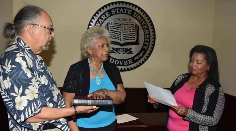 <p>J. Cagney France, fiance of Esthelda Parker Selby, center, holds the bible as she is sworn in as a Board of Trustees member by Board Chairperson Devona Williams.</p>
