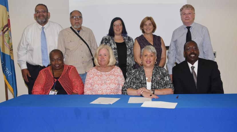 """<p>(Seated l-r) FSCAA&#039;s Bernice Edwards, exec. director, and Dr. Anne Farley, board president; DSU&#039;s Dr. Patrice Gilliam-Johnson, dean of Graduate, Adult and Extended Studies, and Dr. Darren Blackston, <a href=""""mailto:DSU@Georgetown"""">DSU@Georgetown</a> director. (Standing) FSCAA officials Bruce Wright, Cagney J. France and Jaime Sayler; DSU&#039;s Lisa Perelli; and Brad Whaley of the Sussex County Office of Community Development pose after the signing.</p>"""