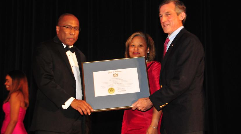 <p>Dr. Harry L. Williams (l), joined by his wife Dr. Robin Williams, receives the Order of the First State from Delaware Gov. John Carney during the Dec. 9 President's Scholarship Ball.</p>