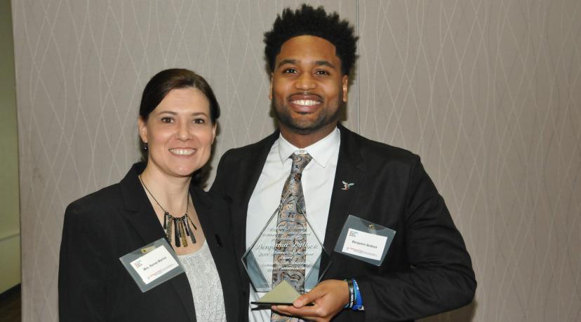<p>Ben Bullock, DSU Mass Comm Class of 2010, receives the Michael J. Feeney Outstanding Alumni Award from presenter Renee Marine, Mass Comm program coordinator.</p>