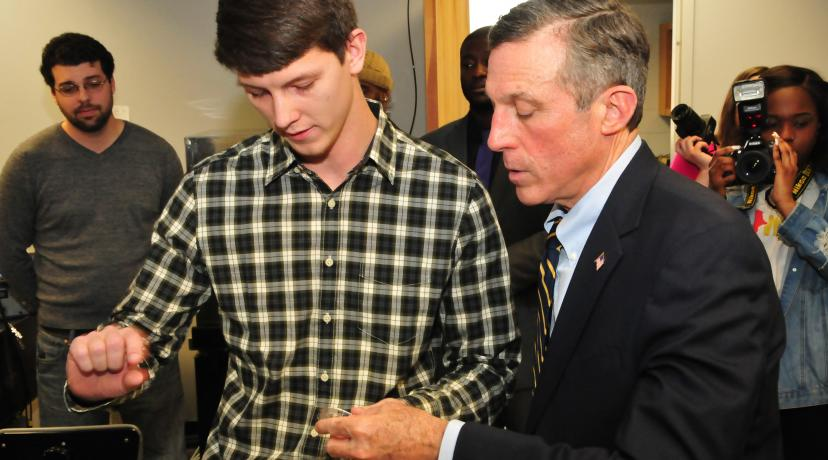 <p>Andrew Voshell (l), graduate engineering students, shows Gov. John Carney a materials sample that is part of some current analytical research he is involved with at DSU.</p>